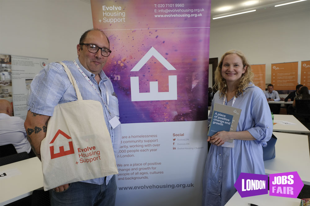 Evolve housing team standing next to team smiling and holding a flyer and a bag with their logo on