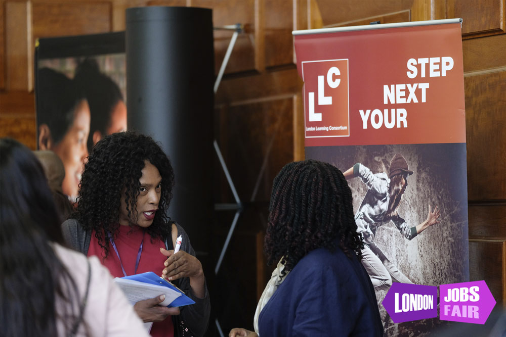 london learning consortium stand at london jobs fair talking to jobseekers
