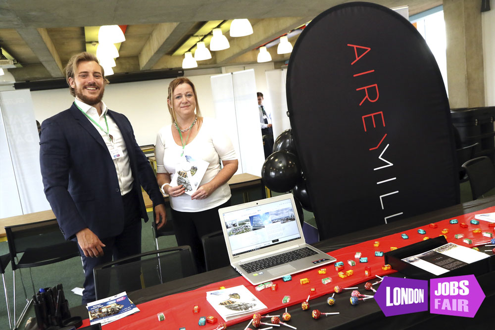 airey miller stand at the jobs fair, 2 people behind stand