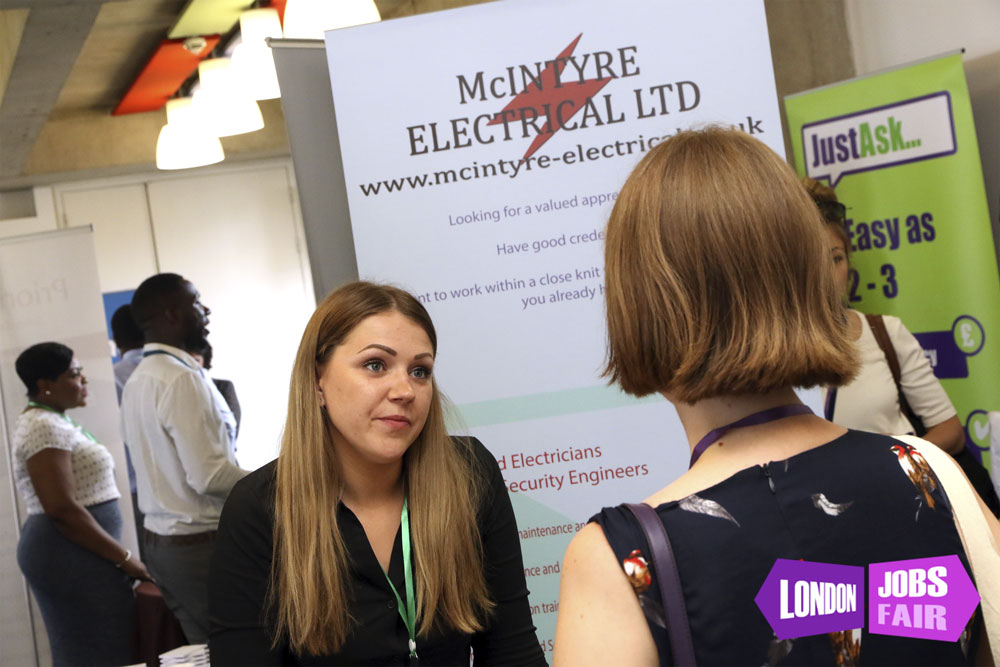 McIntyre Electrical stand at london jobs fair talking to a jobseeker