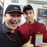 Two people of the KFC team smiling and holding thumbs up
