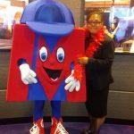 woman standing next to metro bank mascot